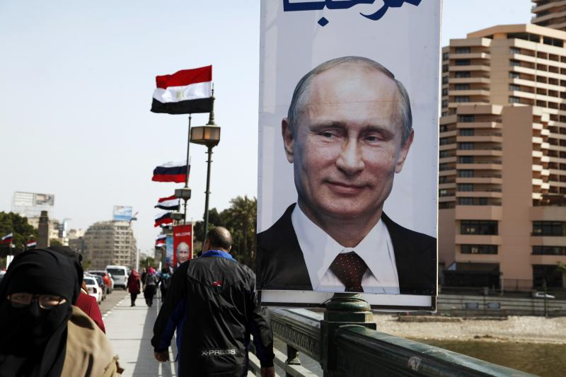 """People walk past a banner with a picture of Russian President Vladimir Putin in central Cairo, February 9, 2015. Putin was due to arrive on his first visit to Egypt in ten years. The banner reads """"Welcome."""""""