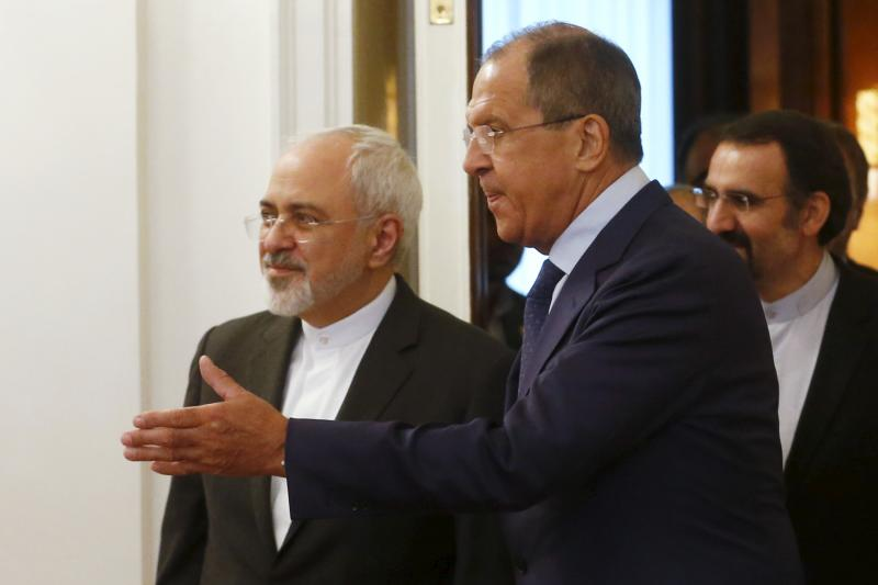 Russian Foreign Minister Sergei Lavrov shows the way to his Iranian counterpart Mohammad Javad Zarif as they enter a hall during their meeting in Moscow, Russia, August 17, 2015.