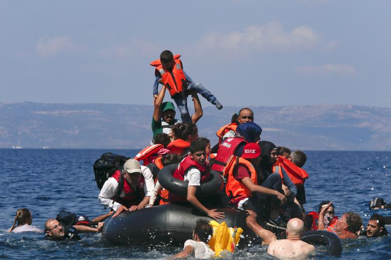 A refugee raises a child into the air as Syrian and Afghan refugees are seen on and around a dinghy that deflated before reaching the Greek island of Lesbos, September 13, 2015.