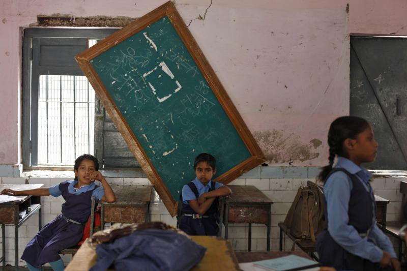 Schoolgirls sit inside their classroom before collecting their free mid-day meals, being distributed by a government-run primary school, in New Delhi May 8, 2013.