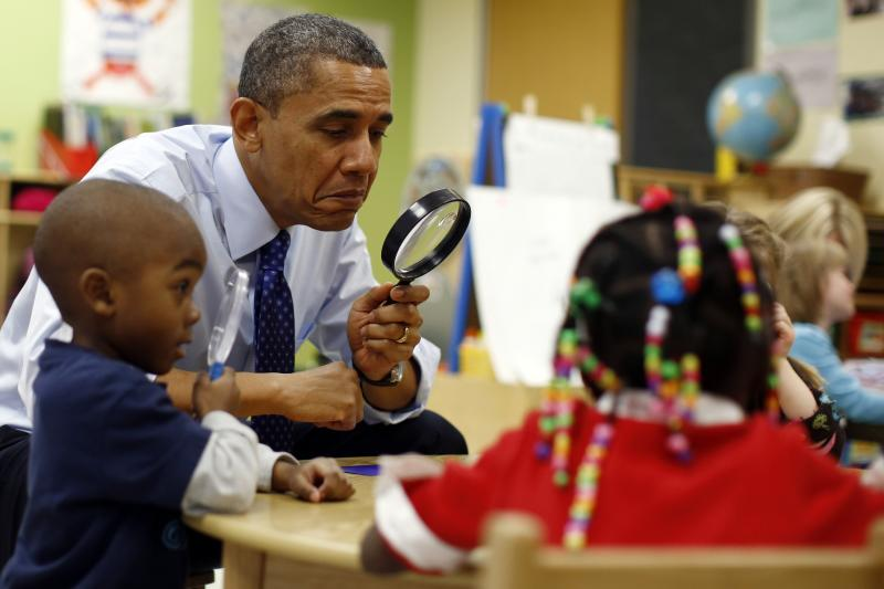 U.S. President Barack Obama uses a magnifying glass to play a game with children in a pre-kindergarten classroom at College Heights early childhood learning center in Decatur February 14, 2013.
