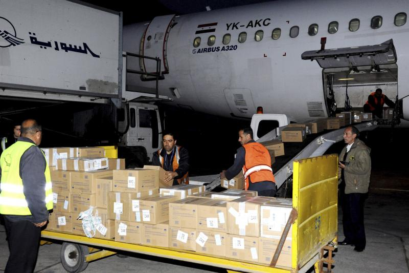 Workers unload humanitarian aid sent from Russia to the Syrian government at Damascus airport, in this handout photograph distributed by Syria's national news agency SANA, January 19, 2014.