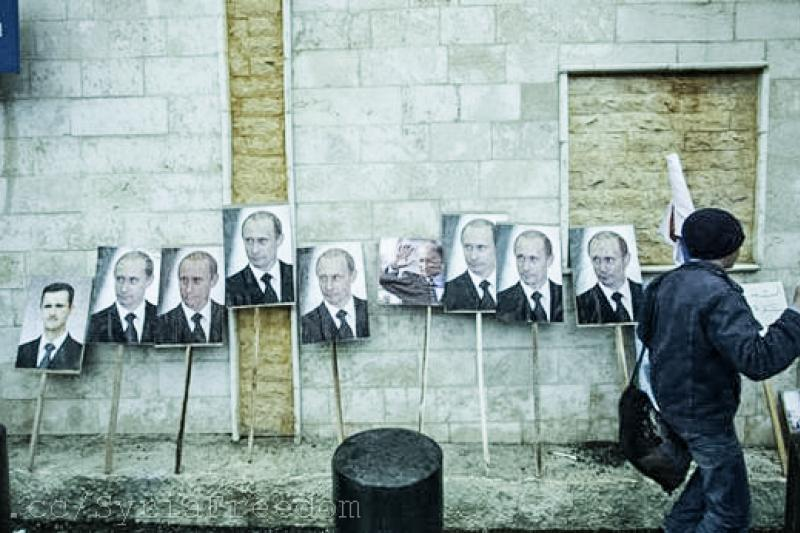 Photos of Syrian President Bashar al-Assad and Russian leader Vladimir Putin are seen during a pro-Assad protest in front of the Russian embassy in Damascus, Syria, March 6, 2012.
