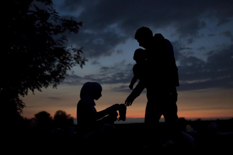 A migrant family waits to board buses on a field near the village of Babska, Croatia September 23, 2015. European Union leaders could promise billions of euros in new funding for Syrian refugees at an emergency summit.