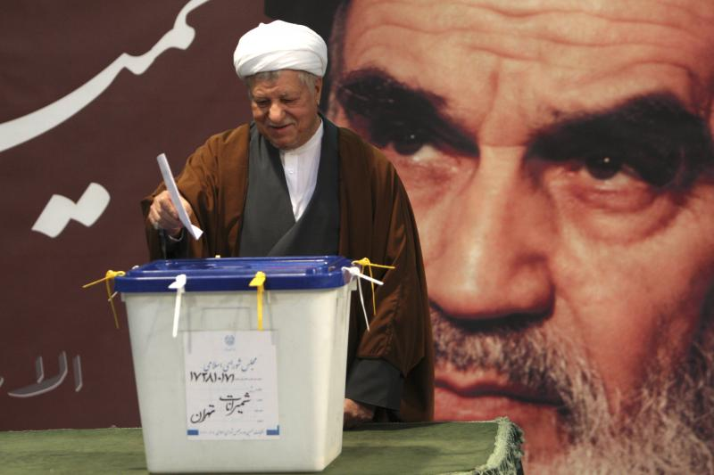 Former Iranian President Akbar Hashemi Rafsanjani casts his ballot in a parliamentary election in Tehran, March 2, 2012. In the background is a poster of Ayatollah Ruhollah Khomeini, the late founder of the Islamic Republic.