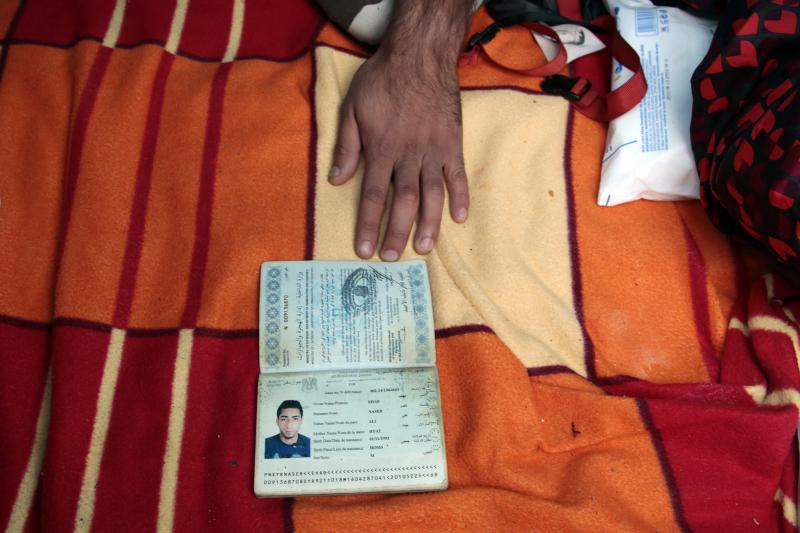 Ehab Ali Naser, a 23 year-old Syrian refugee, displays his Syrian passport in his tent at a makeshift camp on a street, in northern Paris, September 15, 2015.