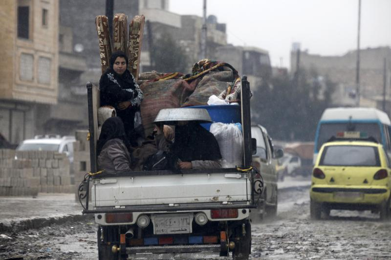 Displaced women sit in the back of a pick-up truck as they flee from Aleppo, February 2013.