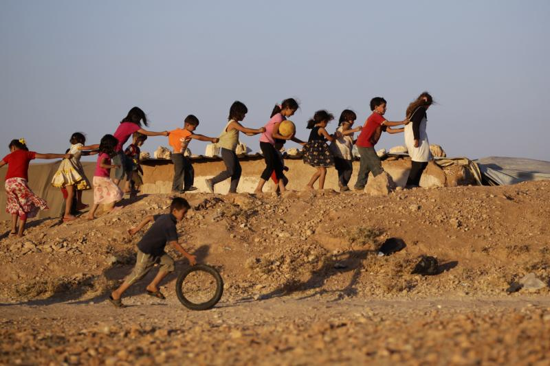 Internally displaced children play inside the Al-Tah camp in the southern Idlib countryside, July 2014.