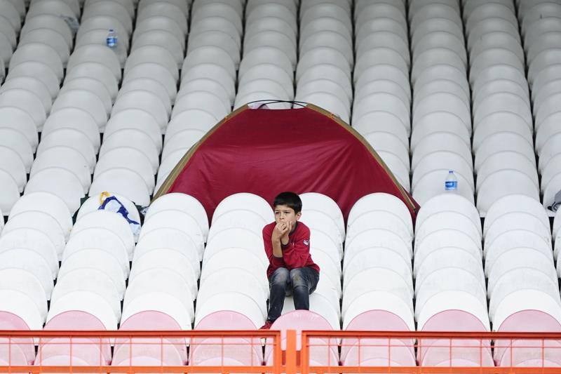 A Syrian boy sits in the stands as he and other migrants wait to be allowed to continue their journey to Greece or Bulgaria, at the Sarayici oil wrestling arena in Edirne, Turkey, September 22, 2015.