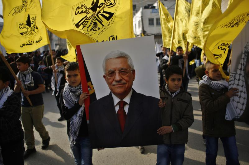 Palestinian boys carry a poster depicting Palestinian President Mahmoud Abbas during a rally marking the 50th anniversary of the founding of the Fatah movement in Ramallah, January 1, 2015.