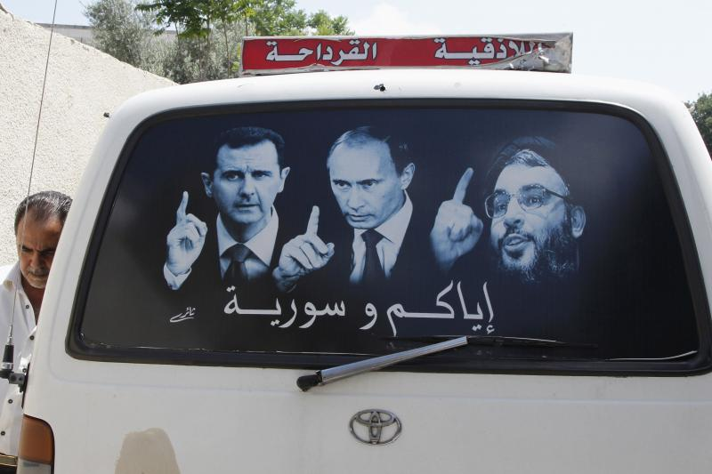 A poster showing Syrian President Bashar al-Assad (L), Russian President Vladimir Putin (C) and Lebanese Hezbollah leader Sayyed Hassan Nasrallah on a micro bus in Syria, May 26, 2014.