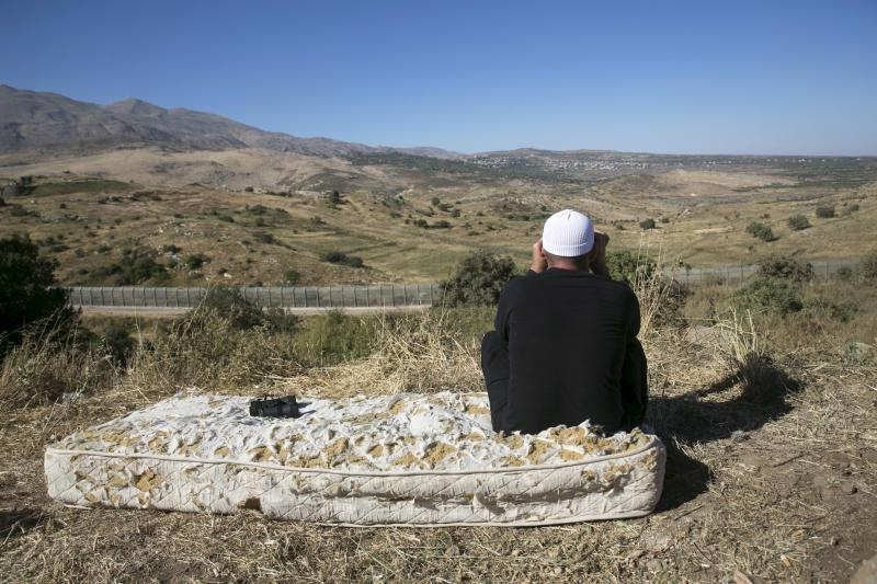 A member of the Druze community uses binoculars to watch the fighting in Syria, from the Israeli side of the border fence between Syria and the Israeli-occupied Golan Heights, near Majdal Shams June 18, 2015.