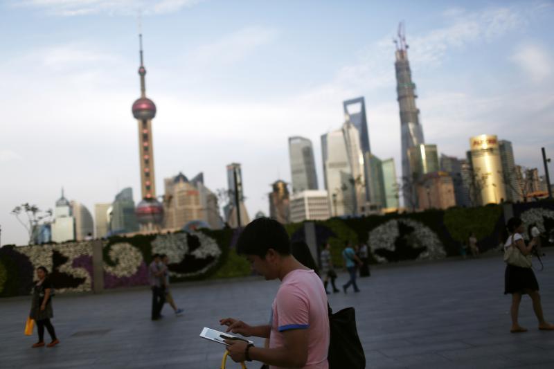 A man checks an iPad on the Bund in Shanghai, September 2013.