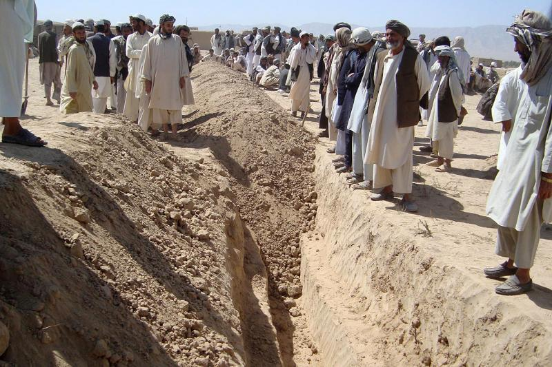 Afghans bury some of the victims of an airstrike in a mass grave near Kunduz, September 4, 2009.