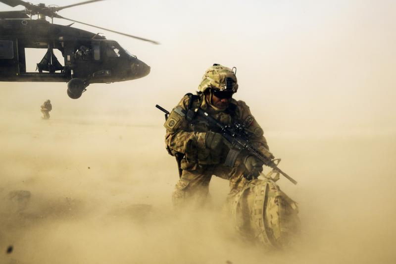 A U.S. soldier shields himself from the rotor wash of a Blackhawk helicopter after being dropped off for a mission with the Afghan police, Afghanistan, December 20, 2014.