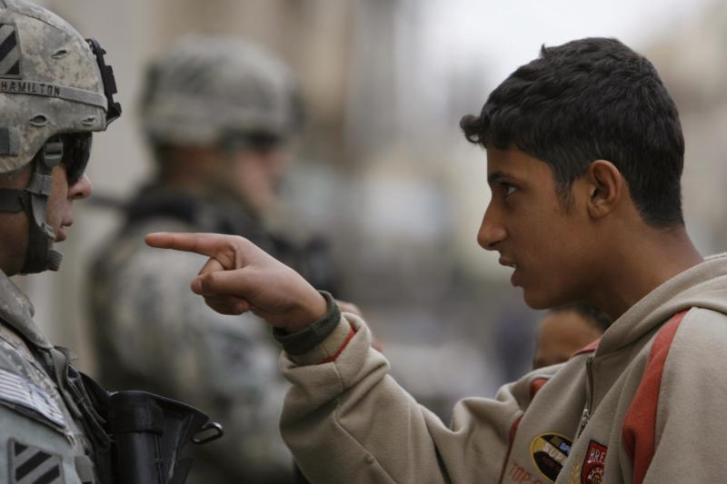 A resident gestures as he talks to a U.S. soldier from 2nd Brigade combat team, 82nd Airborne on patrol in Baghdad's Adhamiya district, January 5, 2008.