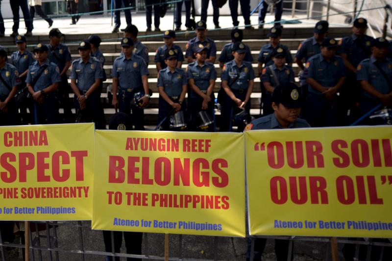 Policemen stand guard behind placards during a rally against China's behavior in the disputed islands in the South China Sea, in front of the Chinese Consulate in Makati, Manila, August 31, 2015.