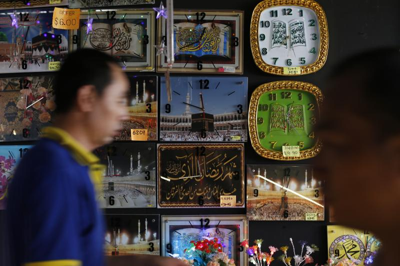 People pass a stall selling clocks, depicting religious verses and pilgrims at the Hajj, at a Hari Raya bazaar, on the eve of Eid al-Fitr, in Singapore July 27, 2014.