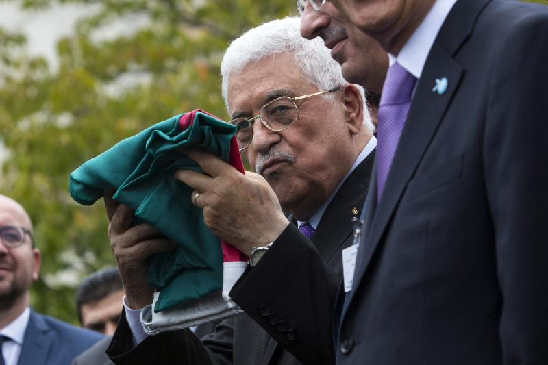 Mahmoud Abbas holds a Palestinian flag at the United Nations in Manhattan, New York, September 2015.