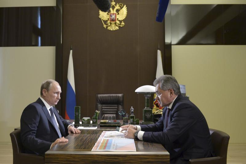Russian President Vladimir Putin (L) meets with Defence Minister Sergei Shoigu at the Bocharov Ruchei residence in Sochi, Russia, October 7, 2015.