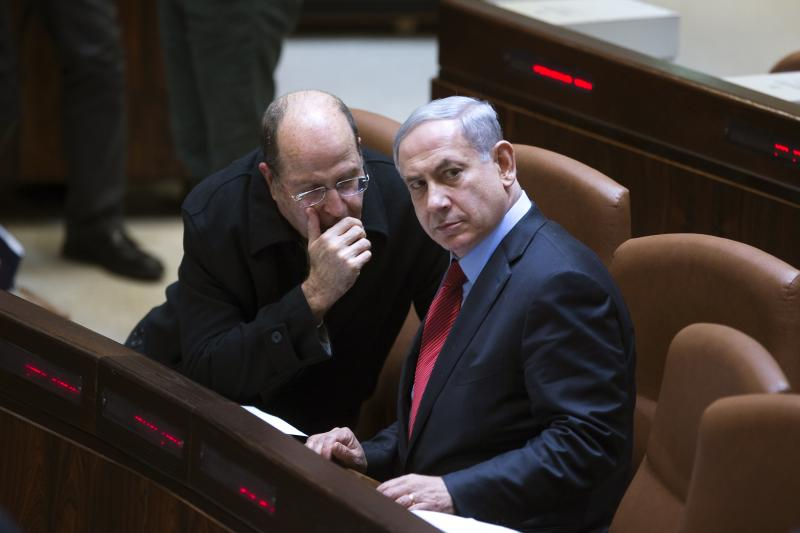 Israeli Defense Minister Moshe Yaalon speaks with Netanyahu during a session of the Knesset in Jerusalem, December 2014. Yaalon and Netanyahu believe that potential losses loom larger than potential gains in the conflict with the Palestinians.