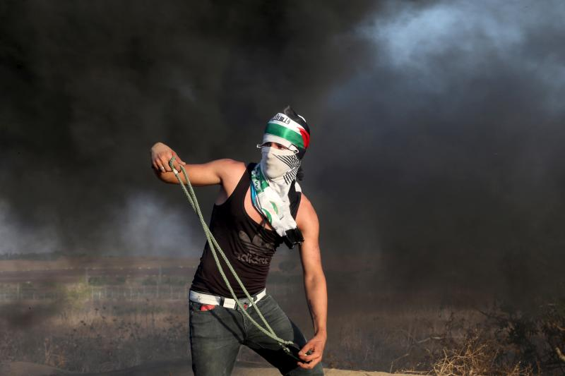 A masked Palestinian protester uses a sling to throw stones at Israeli troops during clashes near the border between Israel and Central Gaza Strip October 14, 2015.
