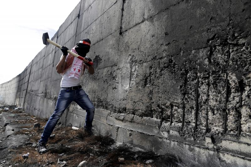 A Palestinian protester tries to hammer a hole through the Israeli barrier that separates the West Bank town of Abu Dis from Jerusalem, during clashes with Israeli troops, October 28, 2015.