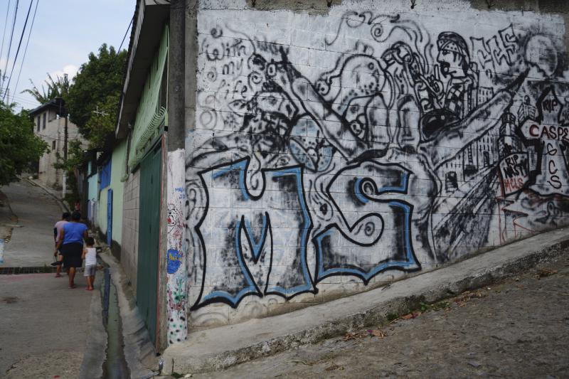 """Two women and a child walk near a wall covered in graffiti and showing the letters """"MS"""", which stand for street gang Mara Salvatrucha, in a neighborhood in San Salvador April 22, 2014."""