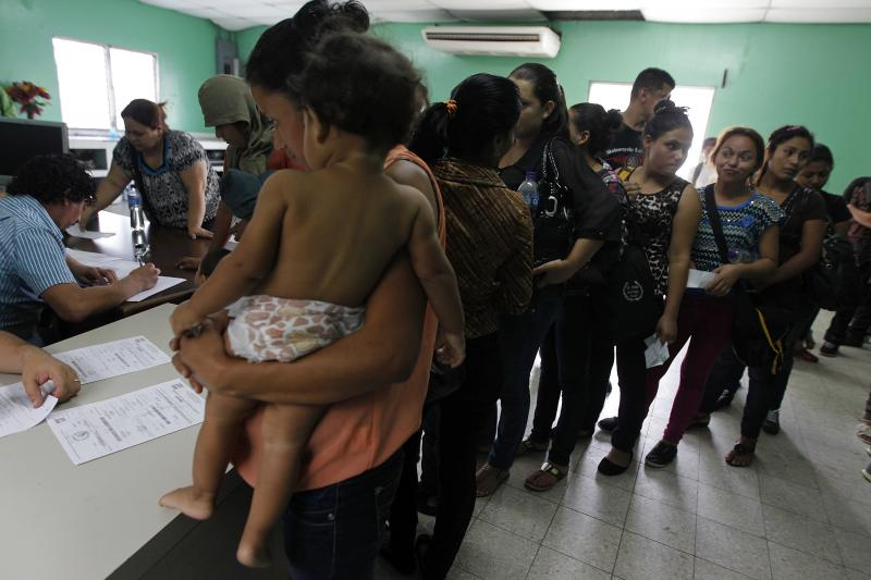 Women and their children wait in line to register at the Honduran Center for Returned Migrants after being deported from Mexico, in San Pedro Sula, northern Honduras June 20, 2014.