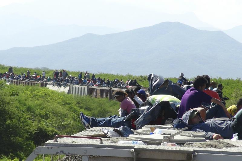 People hoping to reach the U.S. ride atop the wagon of a freight train, known as La Bestia (The Beast) in Ixtepec, in the Mexican state of Oaxaca, June 18, 2014.