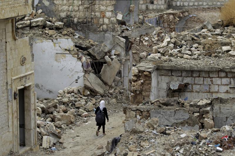 A school girl walks past damaged buildings in the rebel-controlled area of Maaret al-Numan town in Idlib province, Syria October 28, 2015.