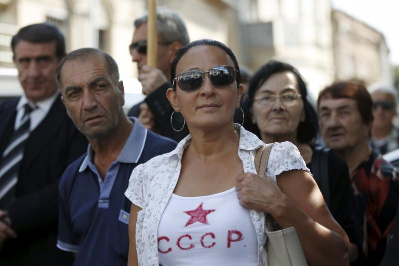 """People attend a pro-Russia rally to demand better bilateral relations, in Tbilisi, September 24, 2015. The Russian letters on the T-shirt reads, """"USSR."""""""