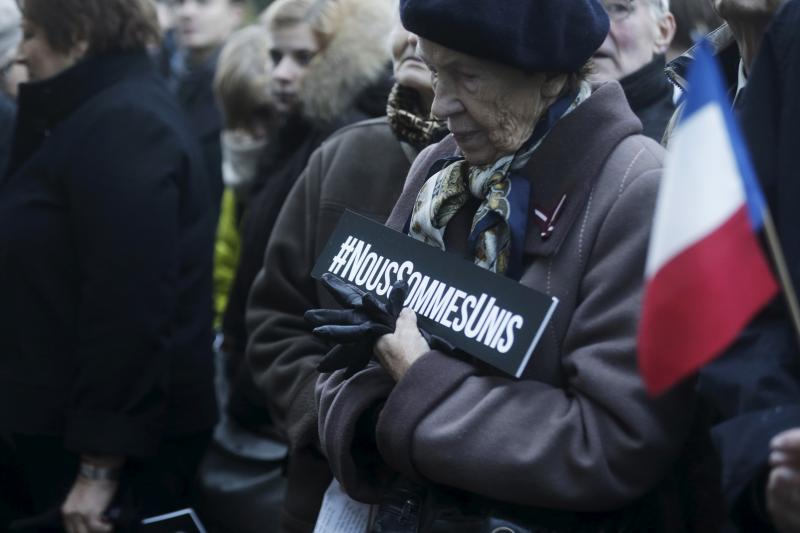 """A woman holds a sign that reads in French """"We are united"""" as she gathers with others in tribute to the victims of Paris attacks near French embassy in Riga, Latvia, November 14, 2015."""