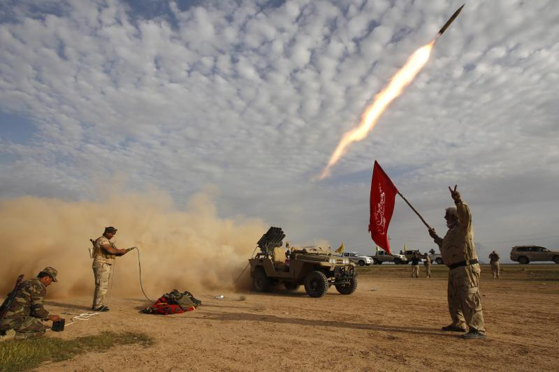 Shiite fighters launch a rocket during clashes with Islamic State militants on the outskirts of al-Alam, March 8, 2015.