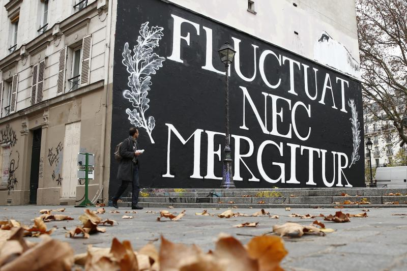 """A man walks past a giant mural with the City of Paris motto """"Fluctuat Nec Mergitur"""", Latin for """"buffeted (by waves) but not sunk"""", in Paris, France, November 17, 2015"""