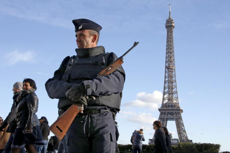 A French police officer stands guard by the Eiffel tower a week after a series of deadly attacks in Paris, France, November 22, 2015.