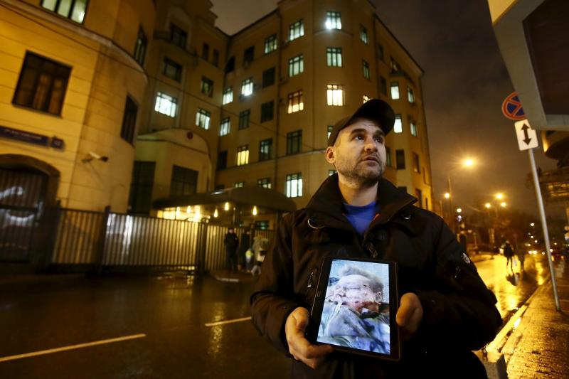 An activist holds a tablet with a picture of the lifeless body of a Russian pilot of a war plane shot down by Turkey, in front of the Turkish embassy in Moscow, Russia, November 24, 2015.
