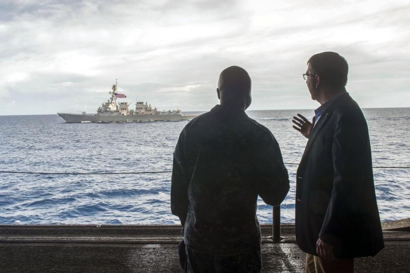 U.S. Secretary of Defense Ash Carter (R) speaks with U.S. Navy Cmdr. Robert C. Francis Jr. aboard the USS Theodore Roosevelt aircraft carrier in the South China Sea, November 2015. The USS Lassen is in the background.