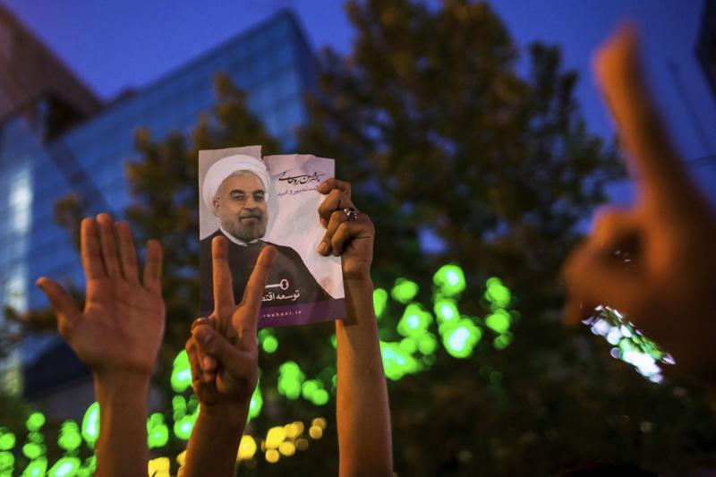 Supporters of moderate cleric Hassan Rouhani hold a picture of him as they celebrate his victory in Iran's presidential election on a pedestrian bridge in Tehran June 15, 2013.