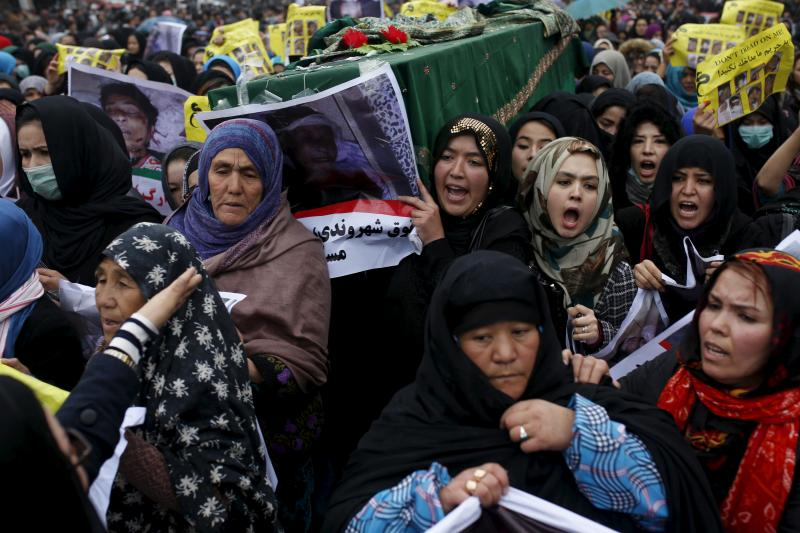 Women carry one of the coffins for the seven people who were killed by unknown militants during a protest procession in Kabul.