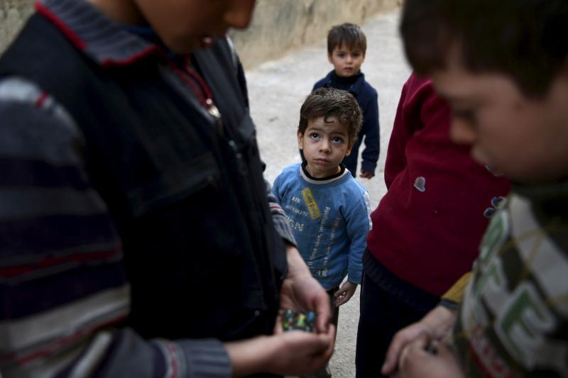 Boys play marbles in the Douma neighborhood of Damascus, Syria, November 26, 2015.