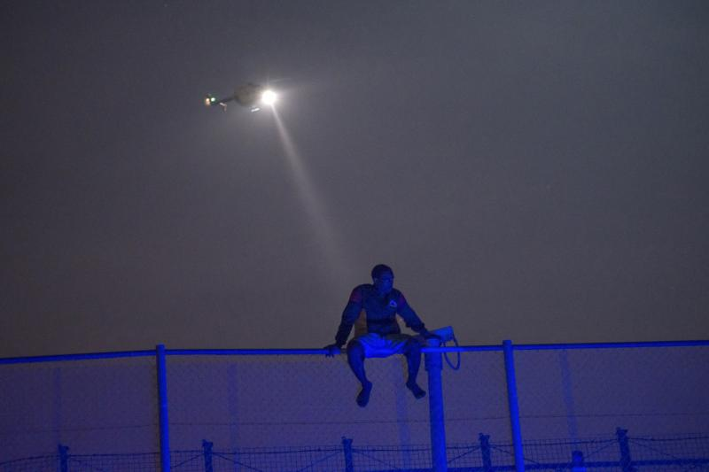 An African migrant sits on top of a border fence covered in razor wire between Morocco and Spain's north African enclave of Melilla, during a latest attempt to cross into Spanish territory, June 14, 2014.