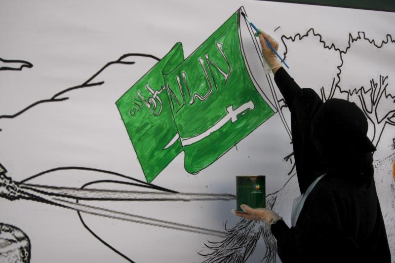 A Saudi woman paints a mural during an activity for national drawings in Jeddah October 29, 2015.