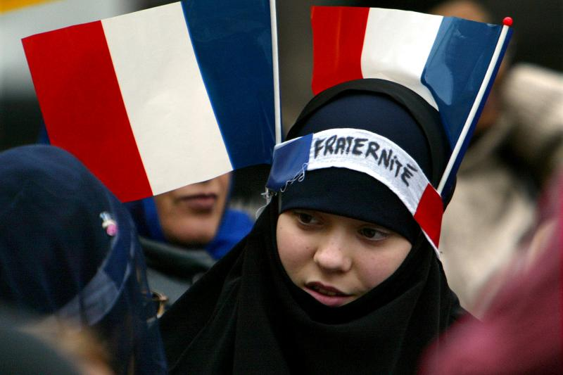 """A young Muslim girl has two French flags and a headband which reads """" Fraternity"""" on her headscarf as she march among about 3,000 Sikhs from across Europe protesting on a Paris boulevard to defend their traditional headgear against a looming French ban on"""