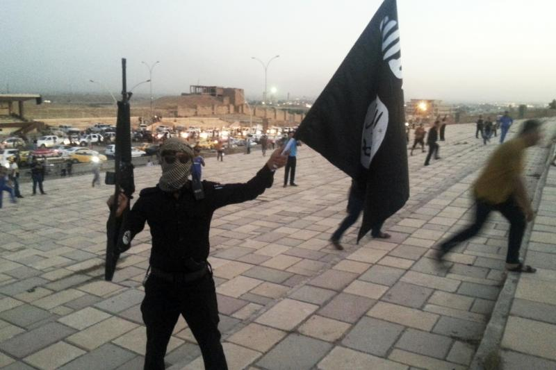 Fighter of the Islamic State ISIS holds a flag and a weapon on a street in the city of Mosul, June 23, 2014.