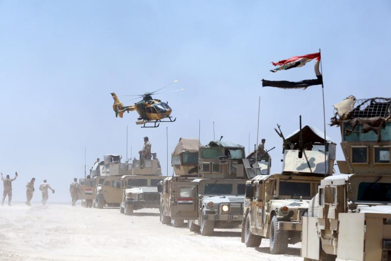 An Iraqi helicopter flies over military vehicles in Husaybah, in Anbar province, July 22, 2015.