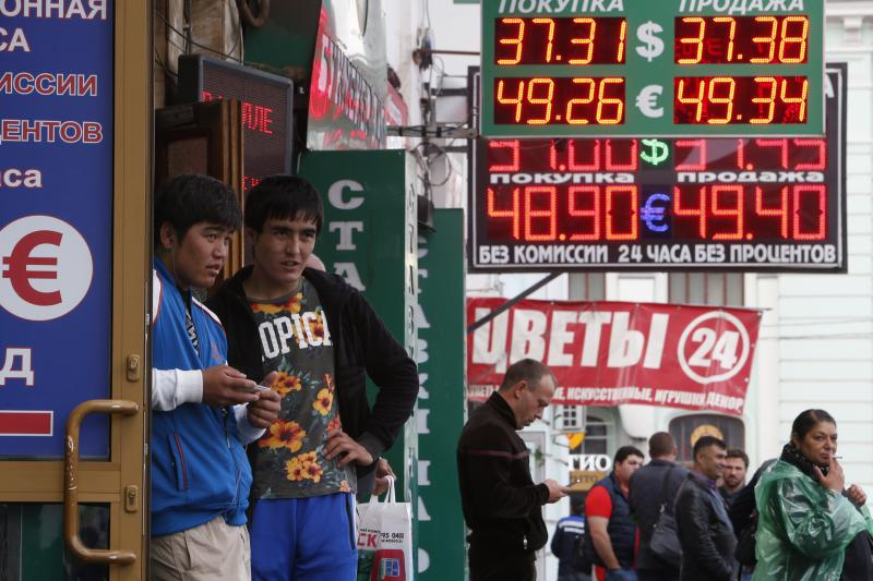 People walk under boards displaying currency exchange rates in Moscow, 2014. Western sanctions coincided with the collapse of global oil prices, worsening, but not causing, Russia's economic decline.