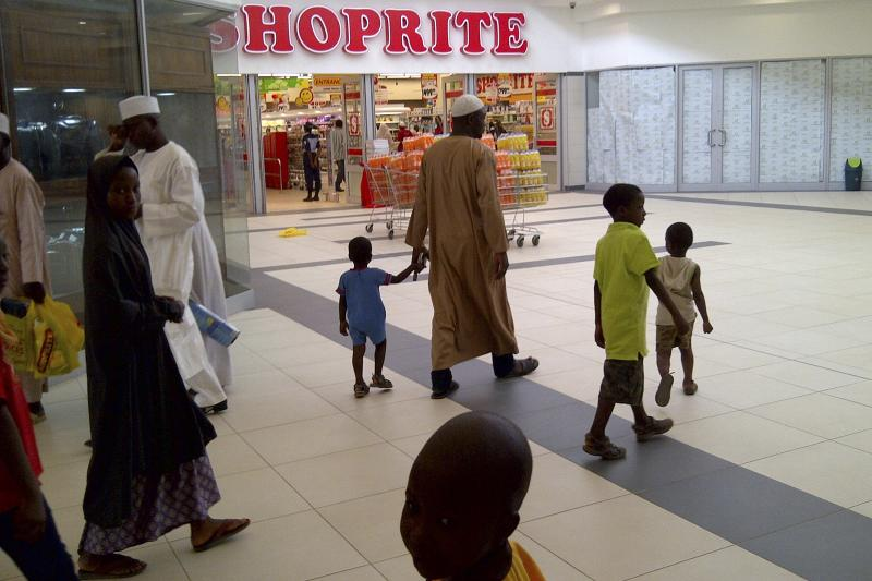 A Nigerian family walks past a newly-opened supermarket in Kano, Nigeria, April 2014. Economic globalization has increased inequality within individual countries.