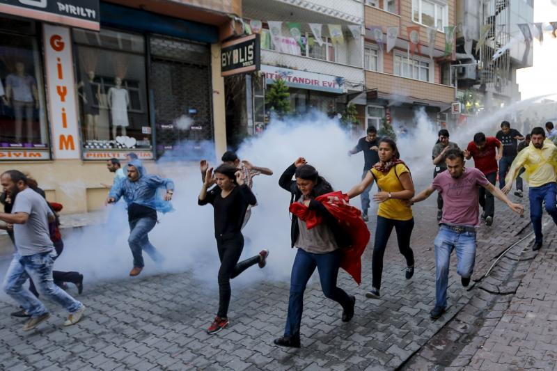 People run from water cannons and tear gas during a protest commemorating Berkin Elvan in Istanbul, June 2015. The Erdogan government has cracked down on the press and sanctioned illegal tactics against polit