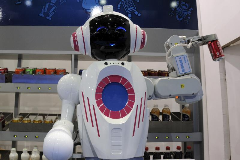 A sales assistant robot picks up a can of Coca Cola during a demonstration at the World Robot Conference in Beijing, China, November, 2015.